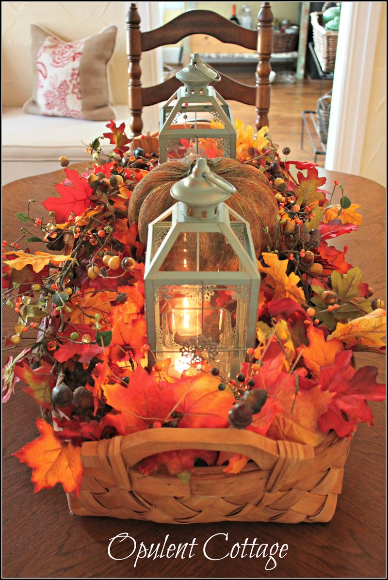 Iconic Fall Decor  The highlight of this arrangement is a paper mache pumpkin flanked by two lanterns. Fall leaves fill in the nooks and crannies of this large woven harvest basket. The soft blue of the lanterns stands out amongst the warm hues of the leaves. This arrangement will look good on your autumn table but would work on your sideboard as well.